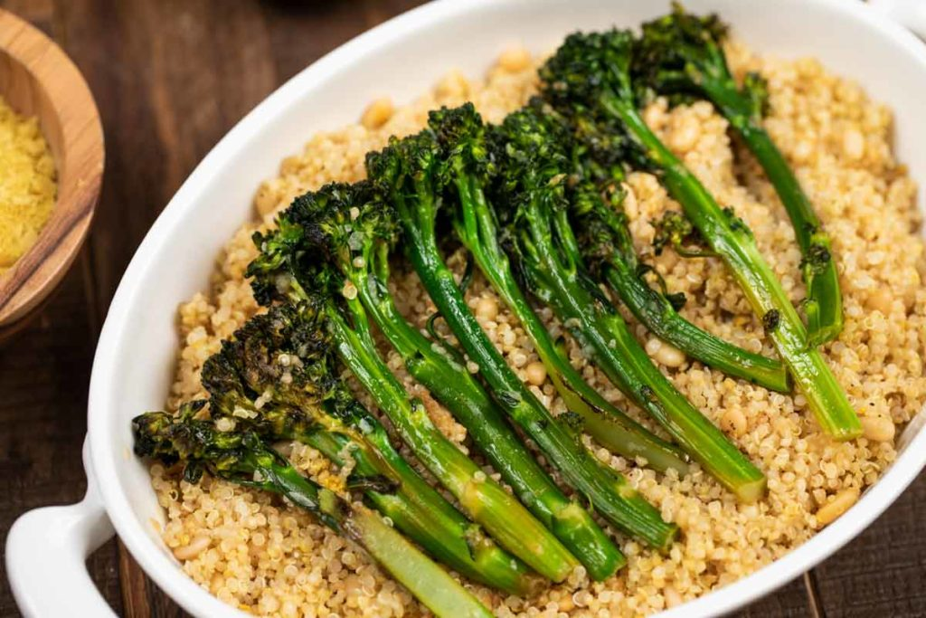 A white dish filled with quinoa topped with charred broccolini.