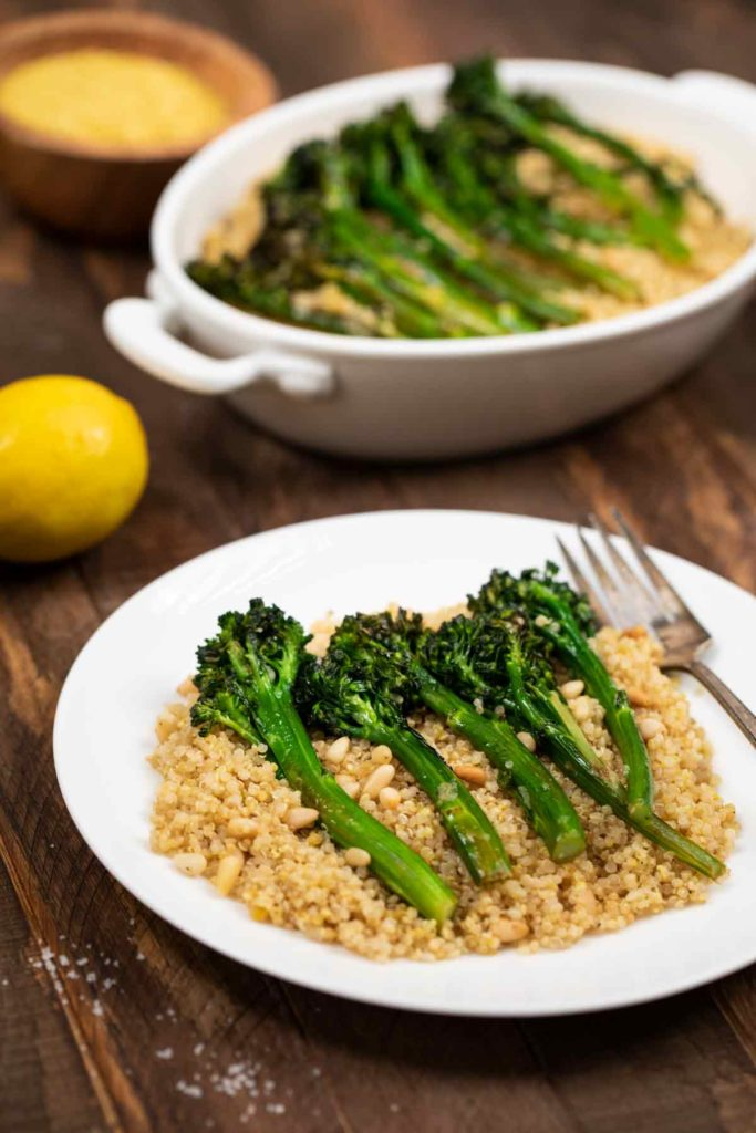A plate filled with quinoa and pine nuts, covered with charred broccolinii.