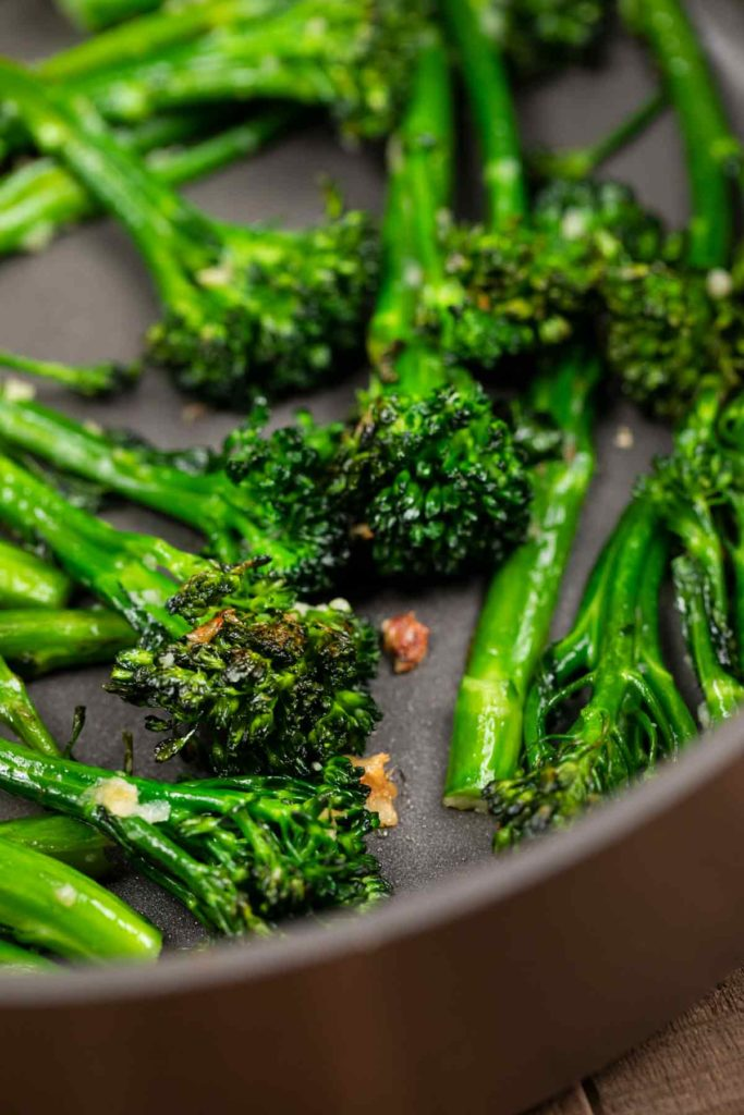 A closeup of a pan of charred broccolini with garlic.