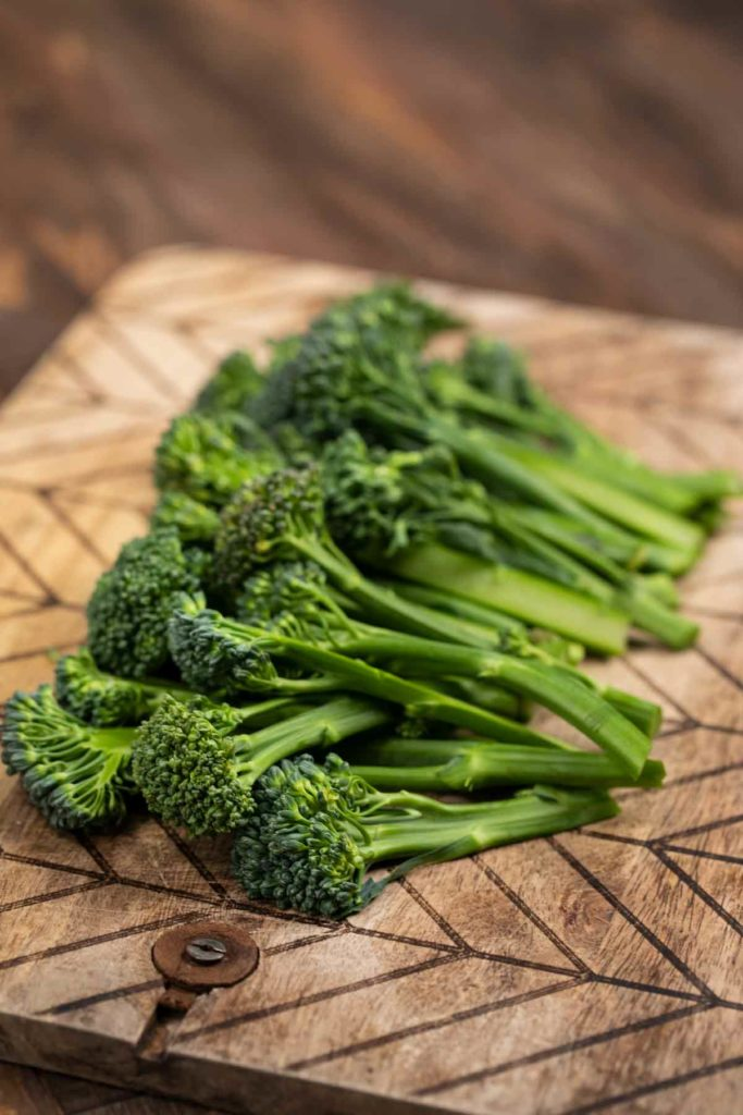 Broccolini on a cutting board, with the bottom 1/3 of the stems cut off.