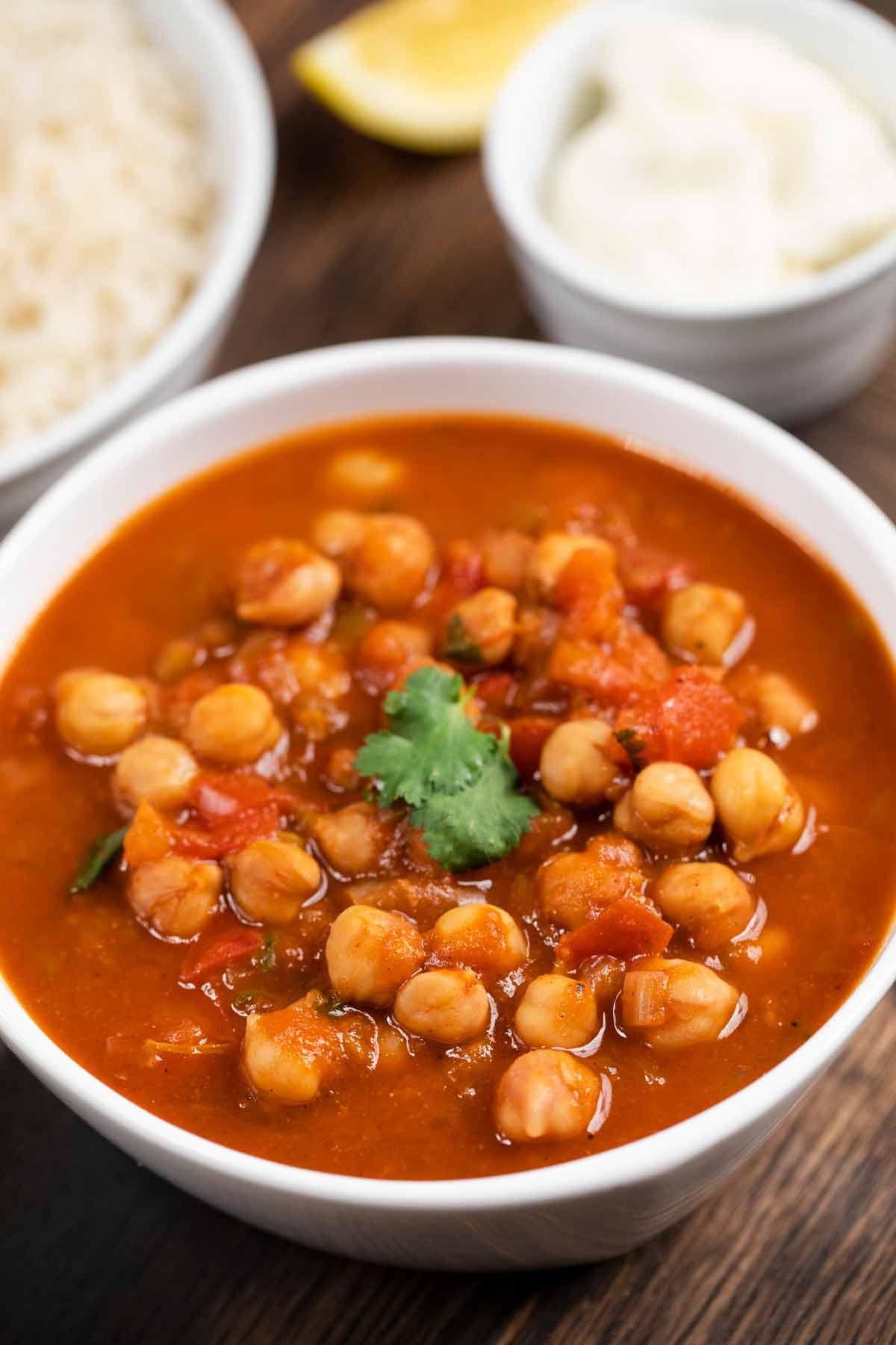 A closeup of a bowl of Instant Pot Chana Masala with chickpeas in a tomato based sauce.