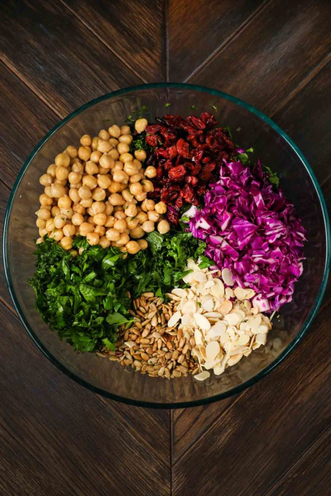 A bowl of chopped kale, cranberries, red cabbage, sliced almonds, sunflower seeds and chickpeas.