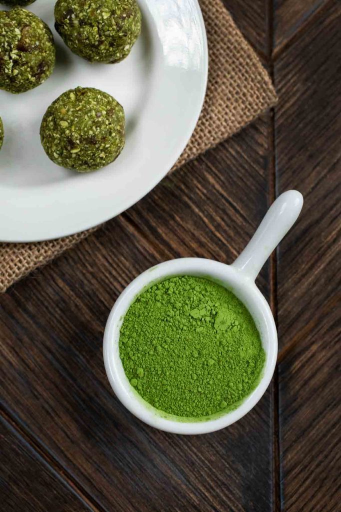 An overhead photo of a small bowl of matcha green tea powder and energy balls on the side.