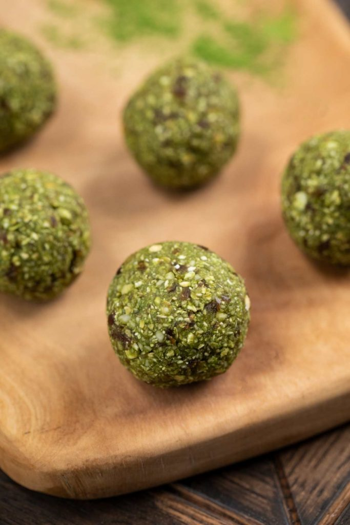 A cutting board filled with matcha green tea energy balls.