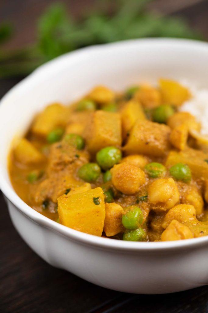 A closeup of vegan Potato Curry in a white bowl.