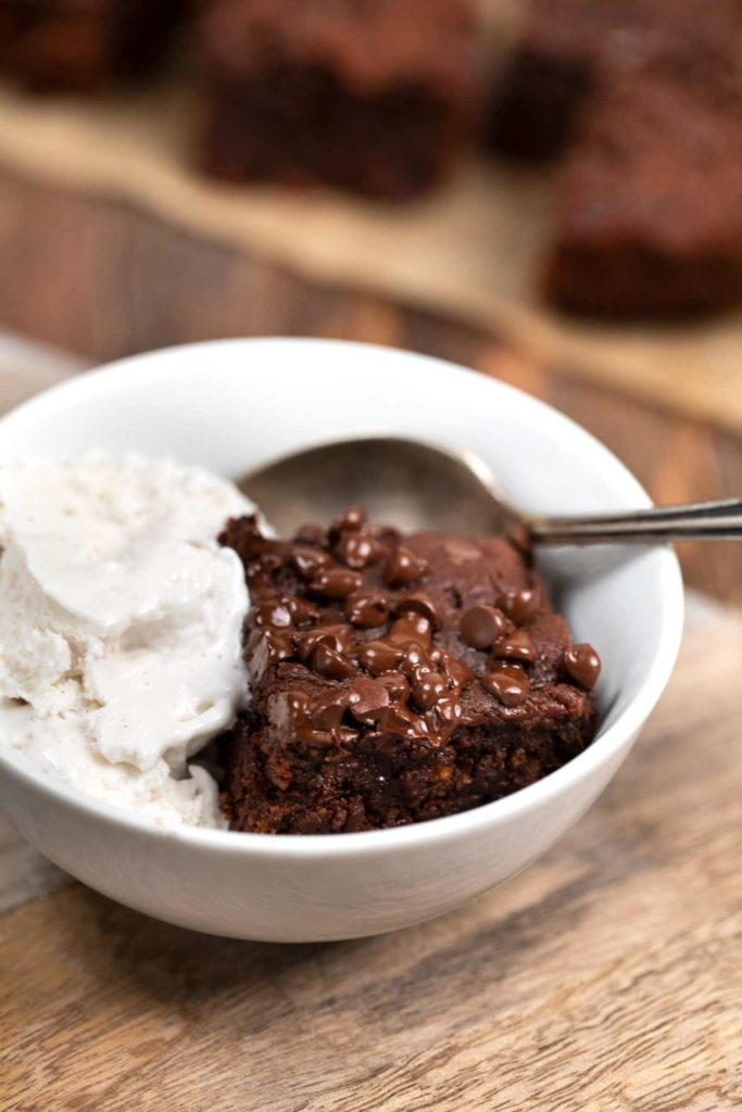 A sweet potato brownie in a white bowl with a side of vanilla ice cream.