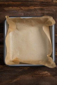 An aluminum baking pan covered in parchment paper.