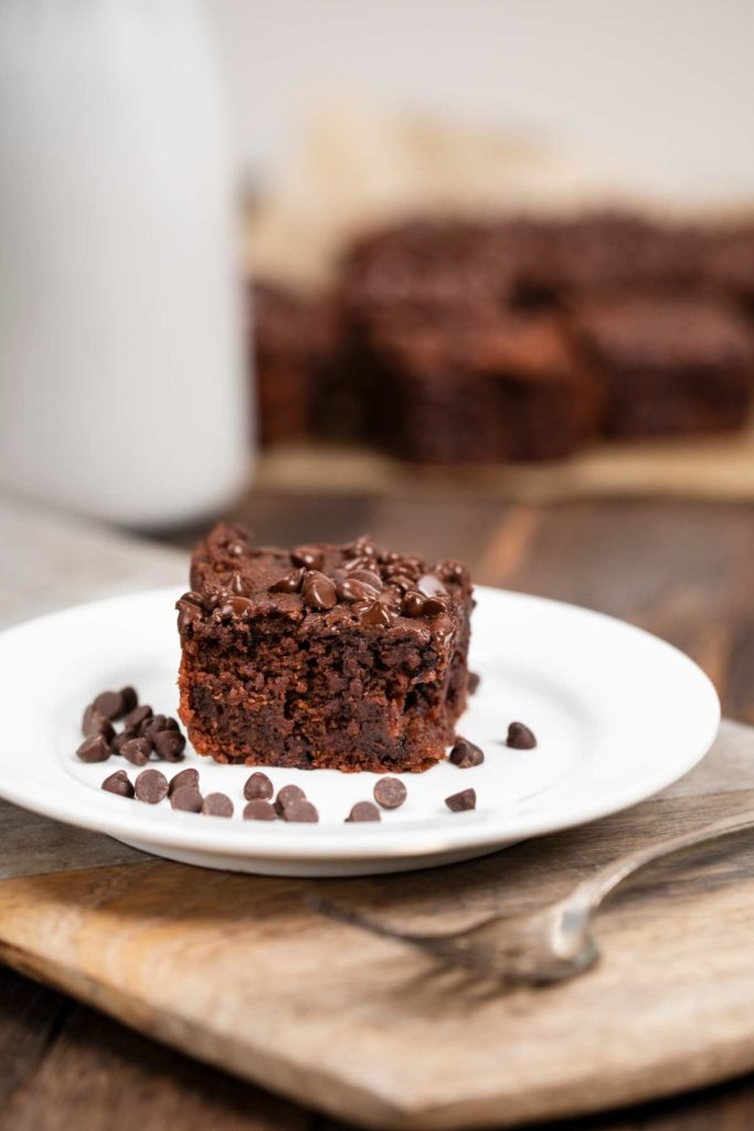 A sweet potato brownie on a plate with chocolate chips on the side, and a glass of milk in the background.