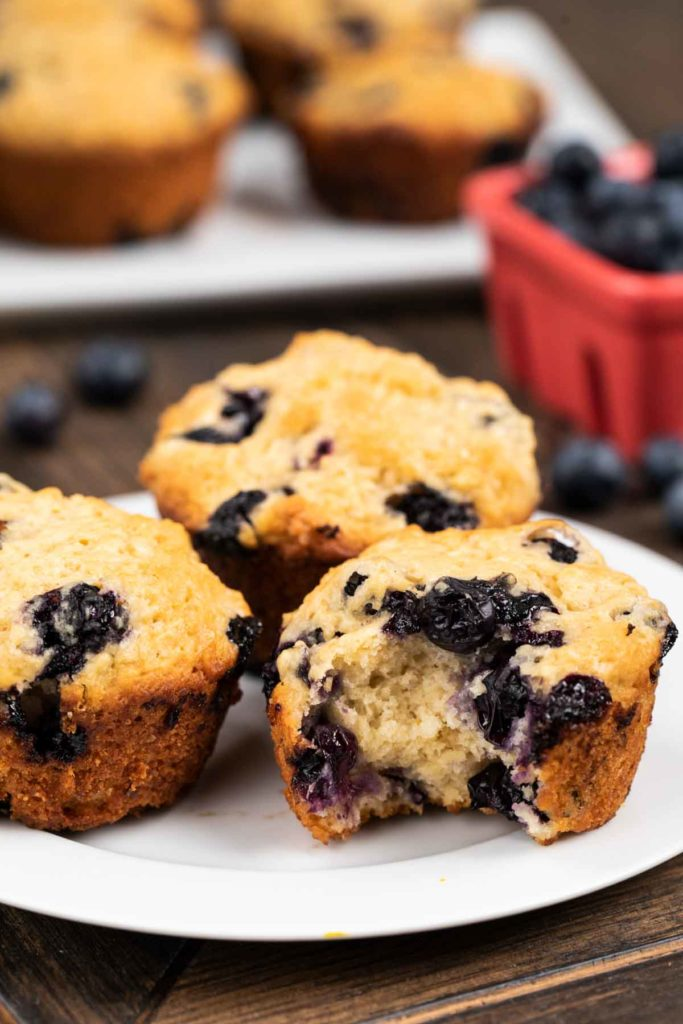 A photo of 3 blueberry muffins on a plate with a bite taken out of one.