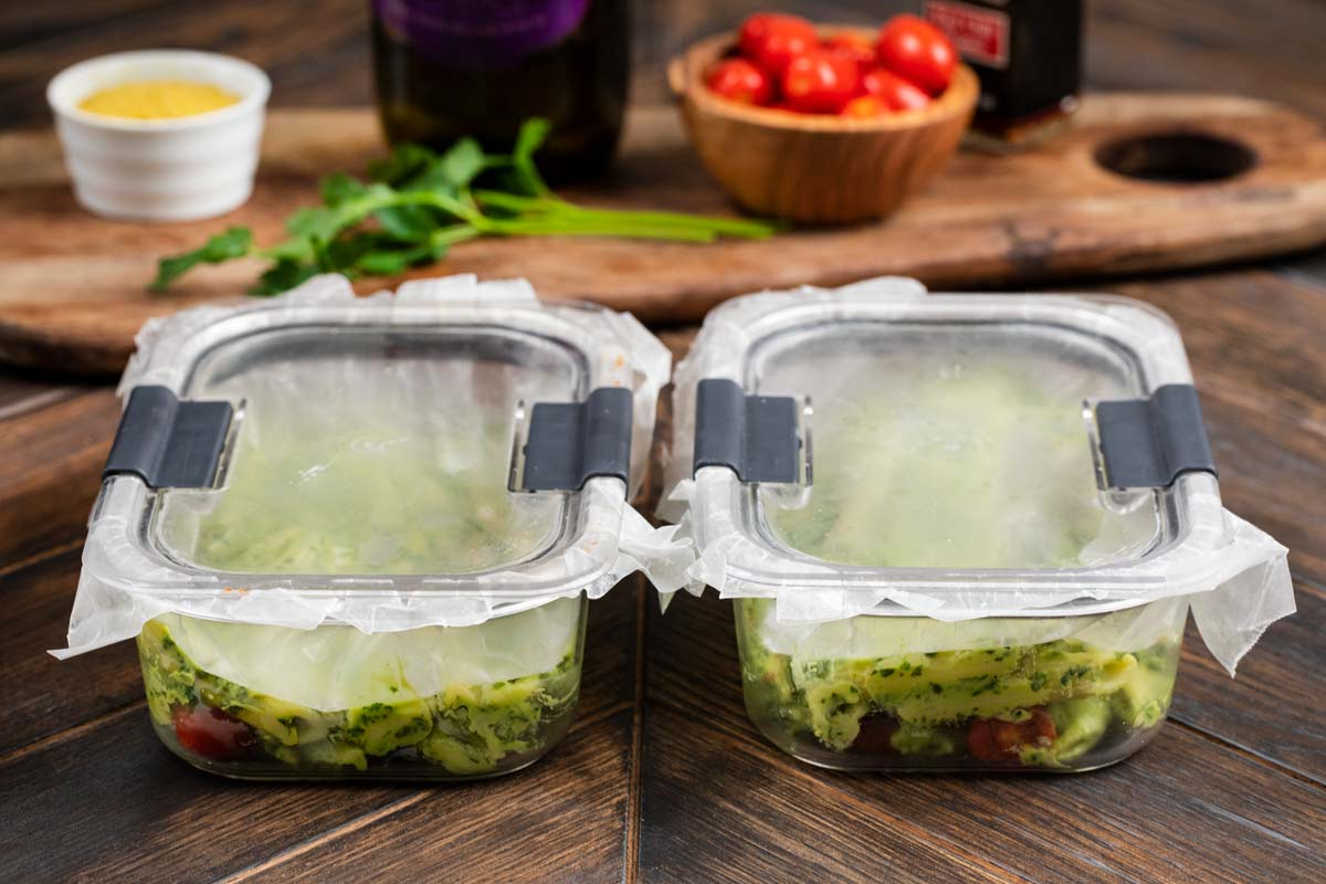 2 containers filled with avocado pasta, topped with wax paper, then the top sealed on, to protect the avocado from getting brown.