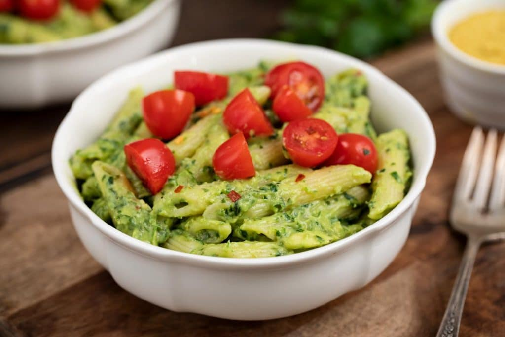 A white bowl filled with avocado penne pasta and cherry tomatoes, with a fork and additional nutritional yeast on the side.