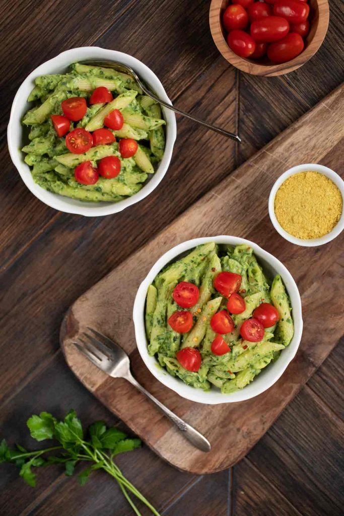 An overhead shot of 2 bowls of avocado cream pasta with a side of nutritional yeast.