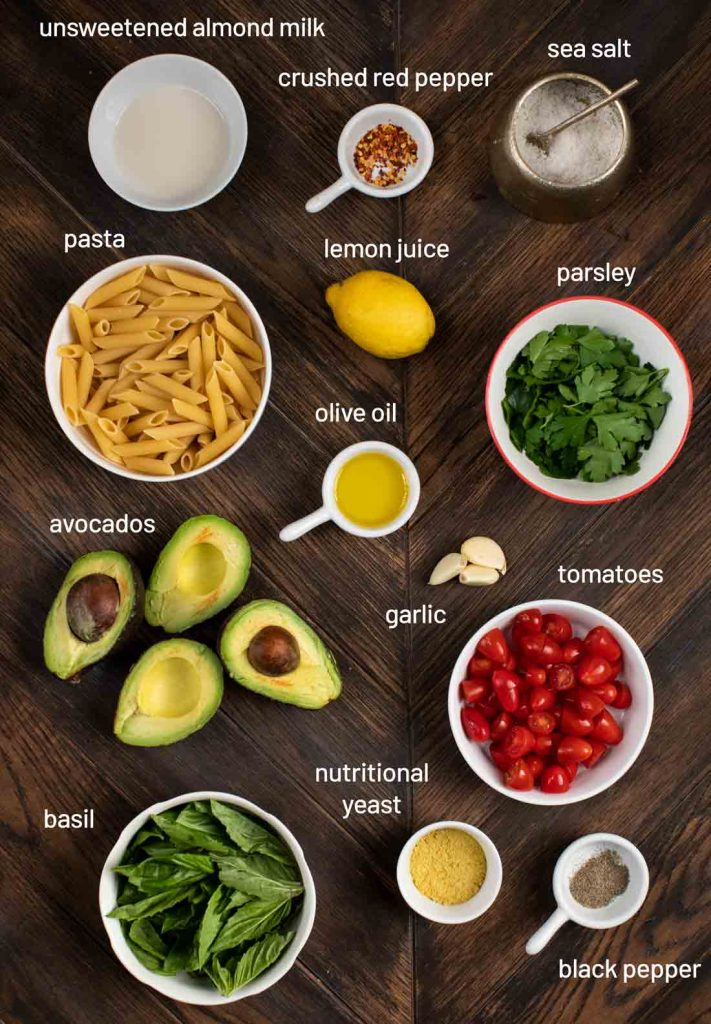 An overhead shot of all of the ingredients for avocado pasta, including almond milk, red pepper, salt, pasta, lemon, parsley, olive oil, avocados, garlic, tomatoes, nutritional yeast, basil and black pepper.