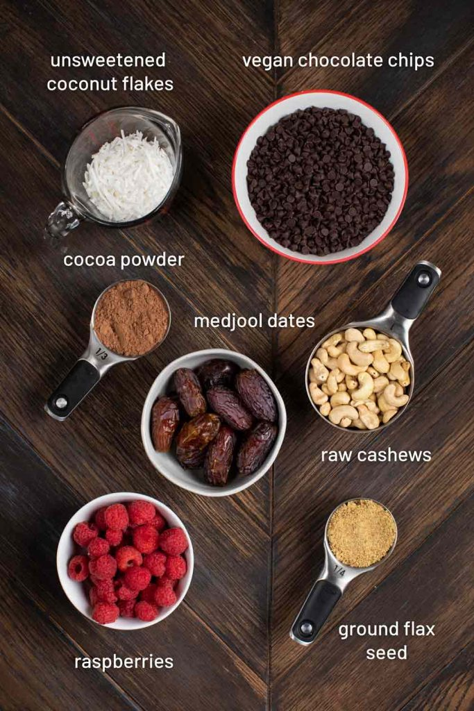 An overhead shot of many ingredients for chocolate raspberry truffles, including raspberries, flax seed, cashews, dates, cocoa powder, chocolate chips and coconut.