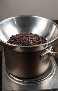 A makeshift double boiler using a pot and a aluminum pan.