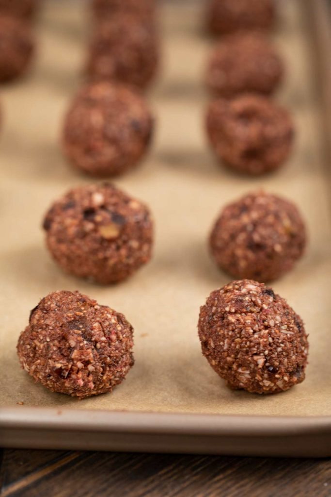 A baking sheet covered in parchment paper covered in chocolate raspberry balls, before freezing.