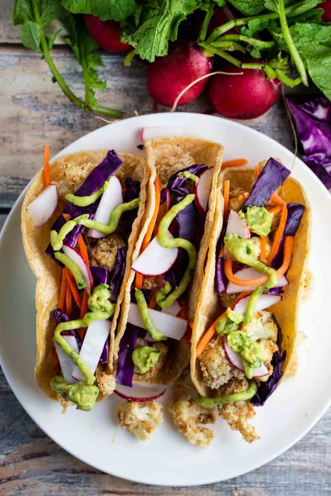 3 cauliflower tacos with avocado lime sauce on top