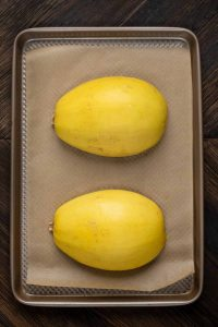 A baking sheet covered in parchment paper, with a squash cut in half face down.