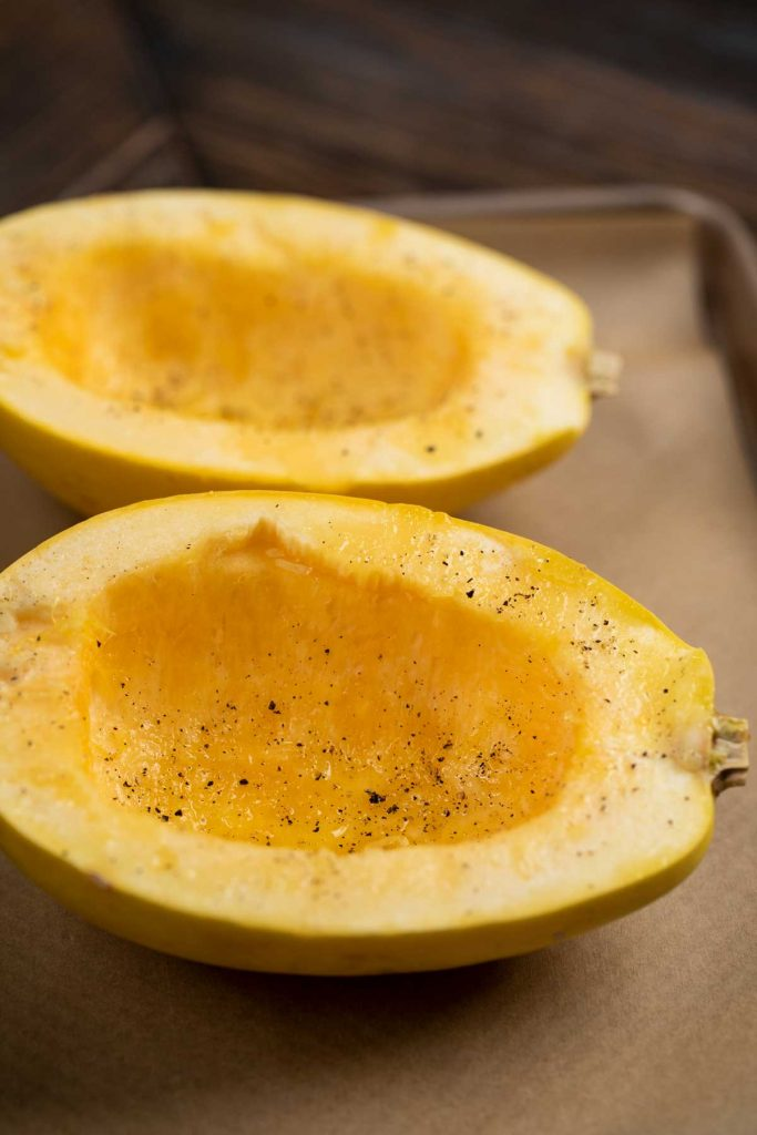 A spaghetti squash cut in half and covered with salt and pepper and olive oil.