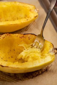 A roasted spaghetti squash with a fork scraping the flesh