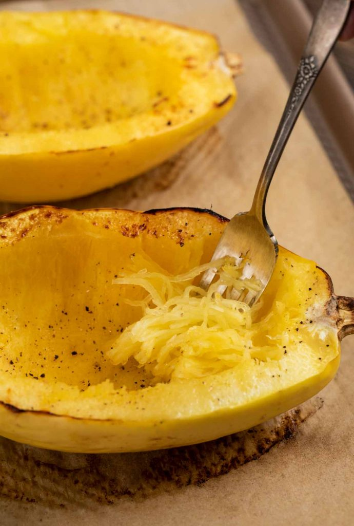 A roasted spaghetti squash, with a fork scraping the strands of the fresh of the fruit.