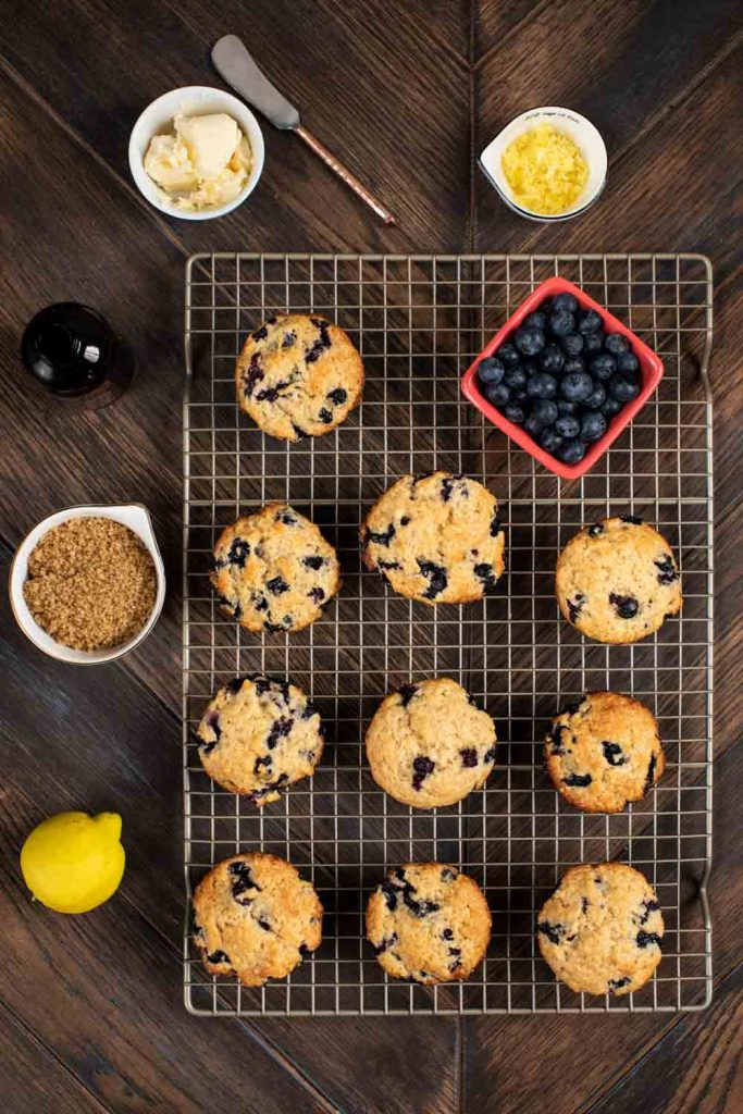 An overhead shot of a pan filled with vegan blueberry muffins, with lemon zest, butter, and flax seeds on the side.