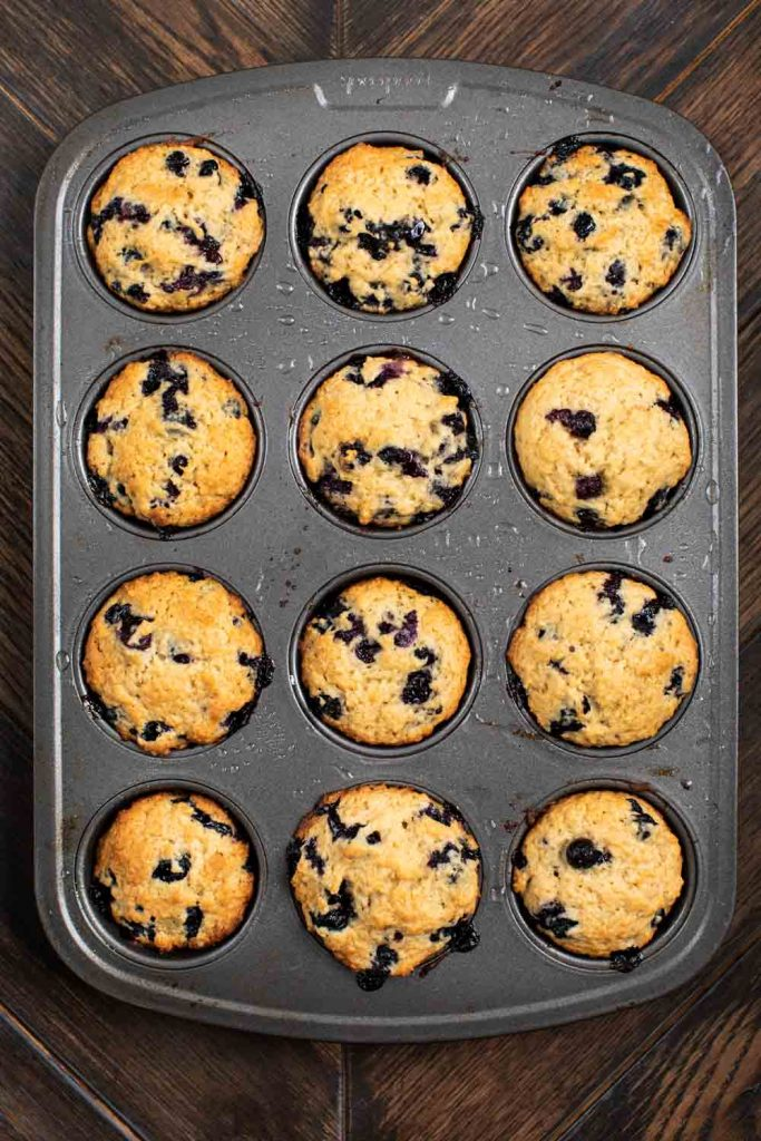 A muffin tin filled with baked vegan blueberry muffins.