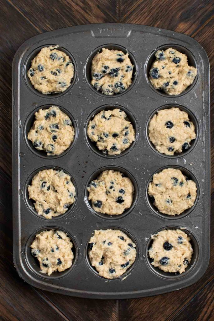 A muffin tin filled with unbaked batter for Blueberry Muffins.