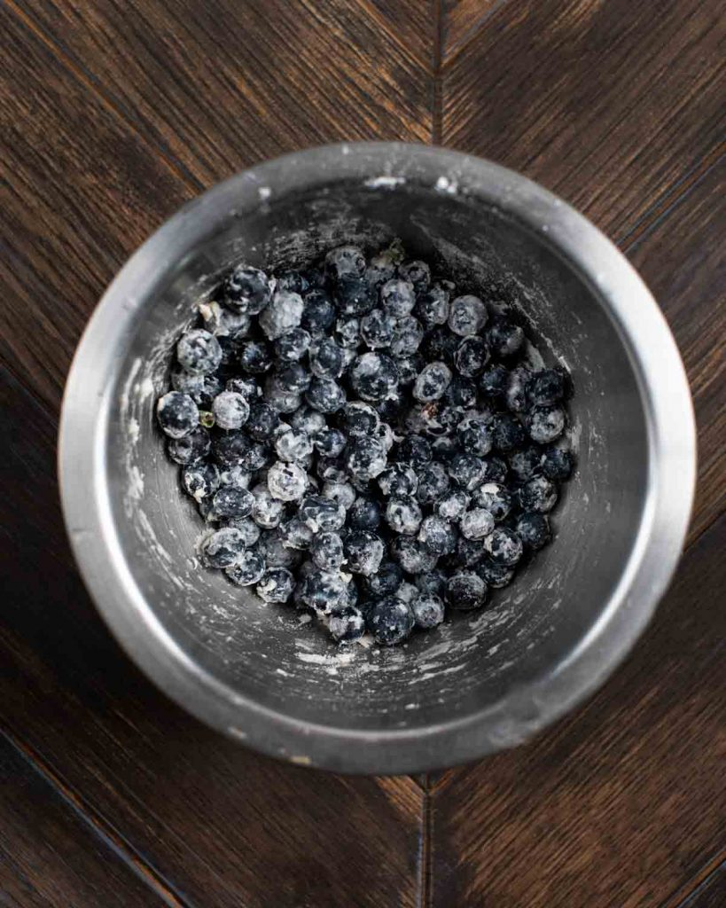 A bowl of fresh blueberries coated with flour.