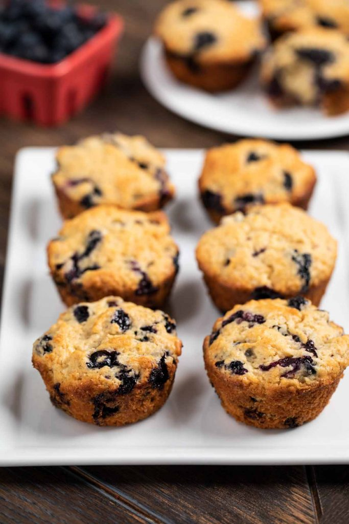 A white plate filled with baked blueberry muffins.