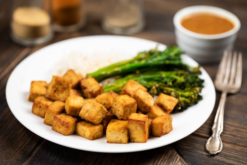 A white plate filled with air fryer tofu with broccolini and white rice in the background of the plate.
