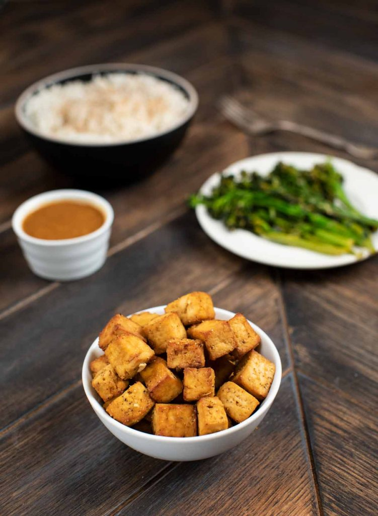 A wide shot showing a small bowl of crispy tofu cubes with a small bowl of sauce, a plate of broccolini and a big bowl of rice in the background.