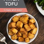 "An overhead image of a white bowl filled with crunchy air fryer tofu with the title of the recipe and the words ""crispy and easy"" below it."