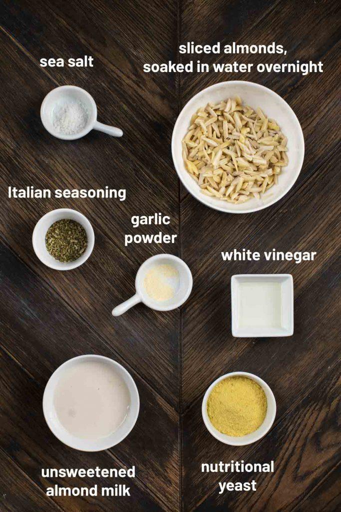 An overhead shot of the ingredients to make Almond Ricotta, such as sea salt, almonds, italian seasoning, garlic powder, white vinegar, almond milk and nutritional yeast.
