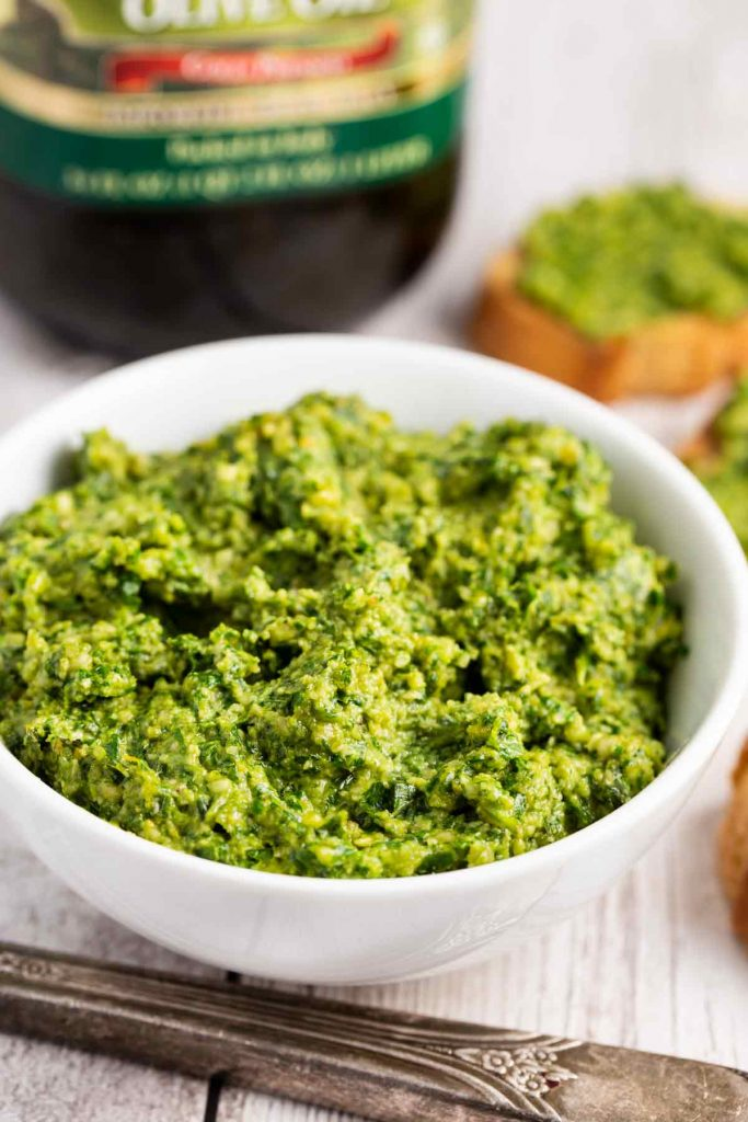A small white bowl filled with arugula pesto with a knife on the side.