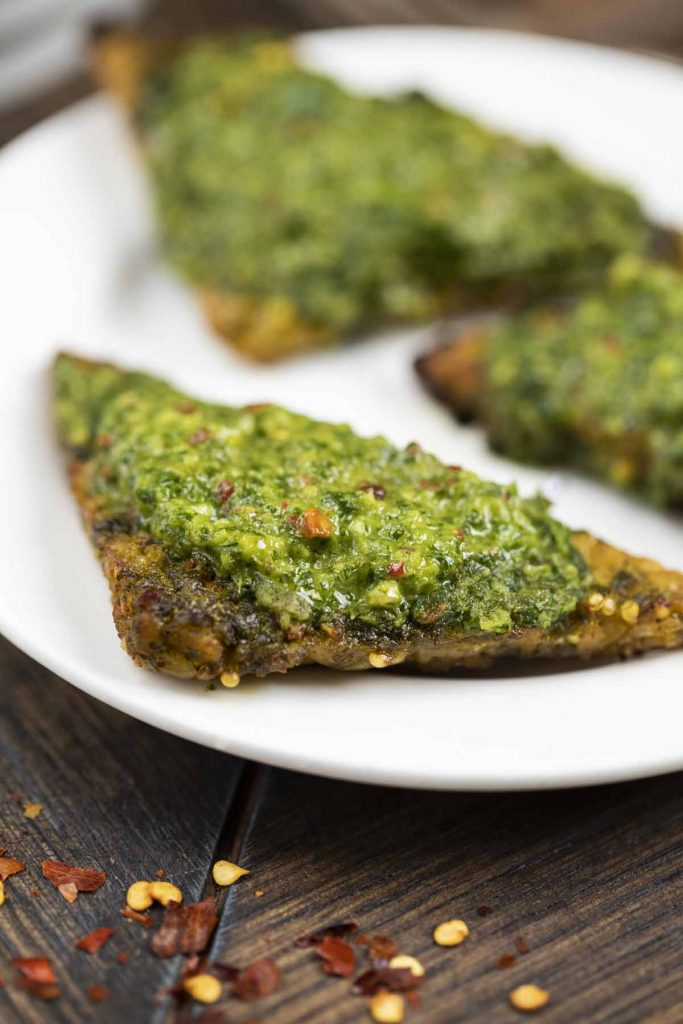A white plate filled with triangle shaped tempeh with chimichurri sauce on top.