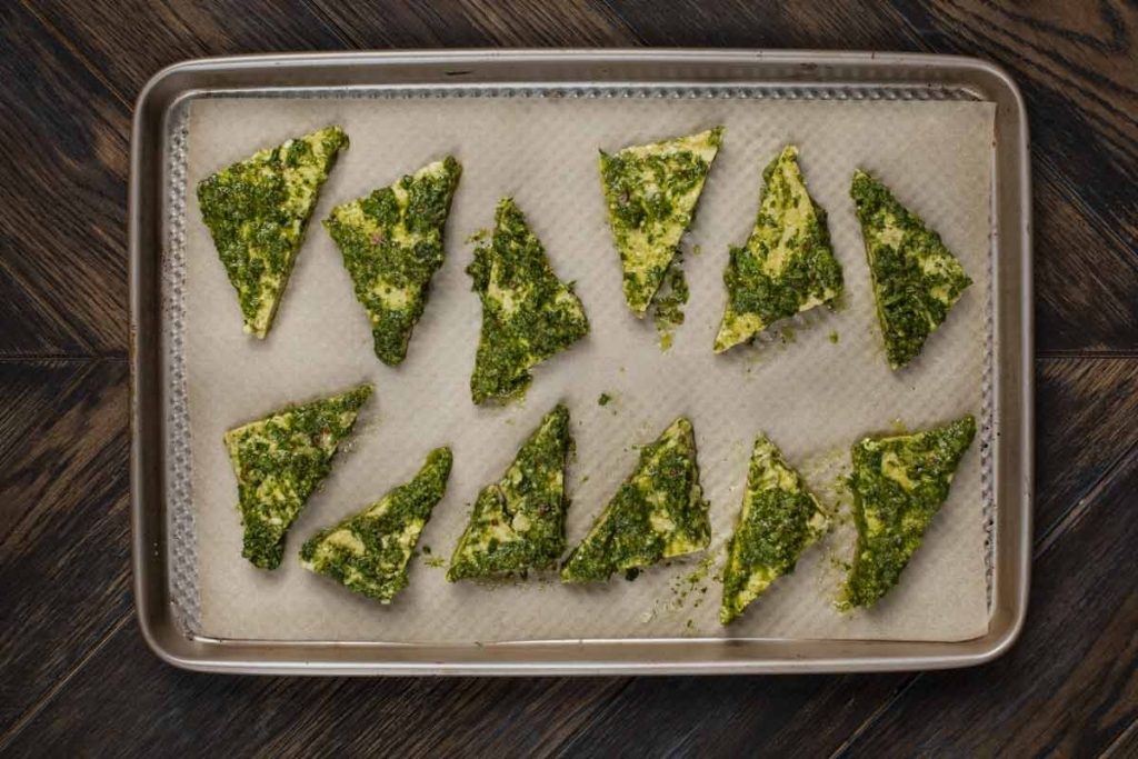 A baking sheet covered in parchment paper and baked tempeh with chimichurri sauce on top.