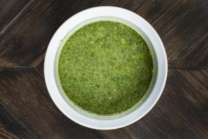 A white bowl filled with chimichurri sauce.