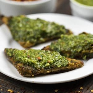 3 pieces of baked Tempeh with Chimichurri Sauce on top, on a white plate.