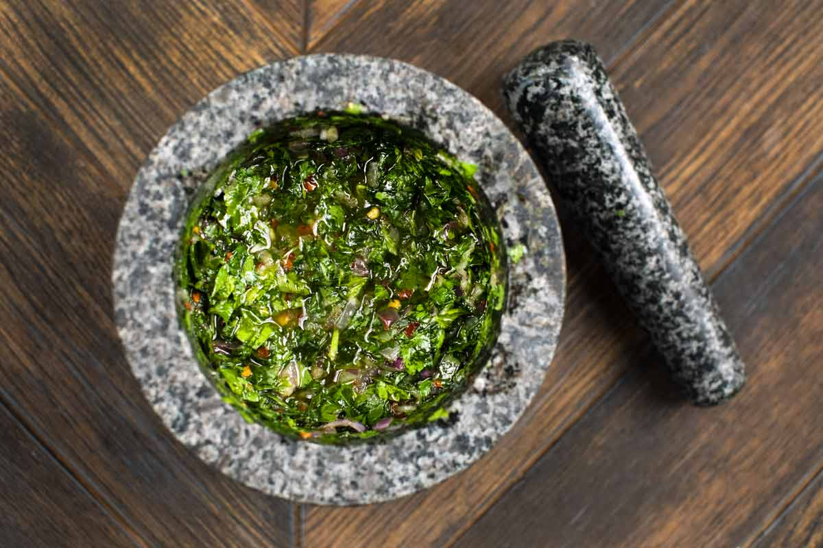 A mortar filled with chimichurri sauce and a pestle on the side.