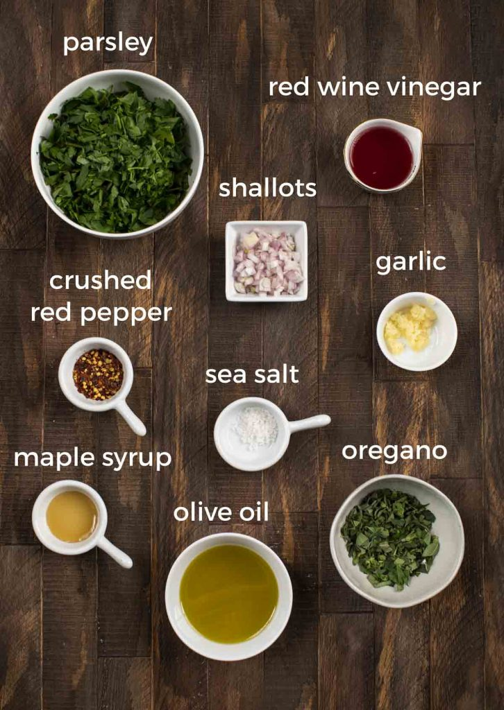 A bunch of white bowls on a wood background with ingredients for chimichurri sauce, including parsley, red wine vinegar, shallots, crushed red pepper, garlic, salt, oregano, olive oil and maple syrup.