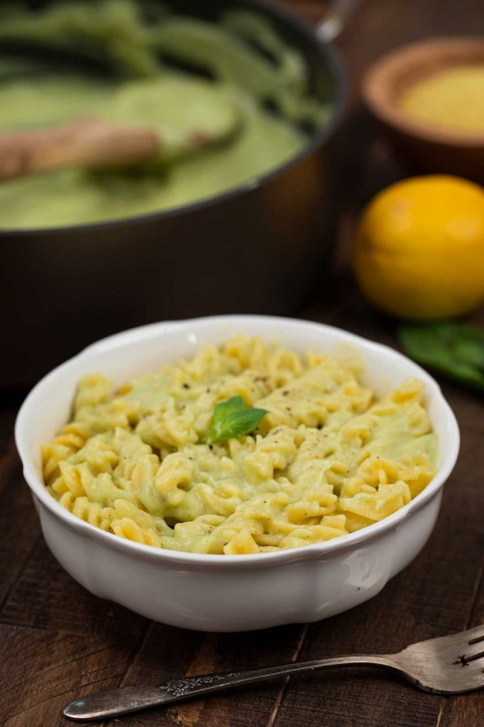 A white bowl filled with corkscrew pasta noodles mixed together with cauliflower pasta sauce.