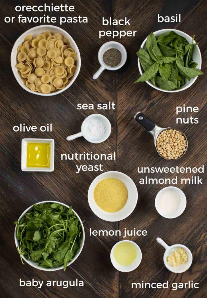 An overhead shot of ingredients displayed on a wooden background; pasta noodles, black pepper, basil, olive oil, salt, pine nuts, nutritional yeast, almond milk, arugula, lemon juice and garlic.