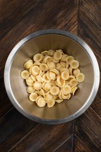 A stainless steel bowl filled with orecchiette cooked pasta.
