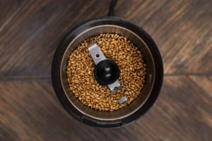 An overhead shot of a coffee grinder filled with whole flax seeds.