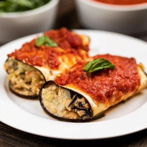 A white plate with 2 pieces of eggplant roll up casserole on top, with fresh basil and a side of sauce.