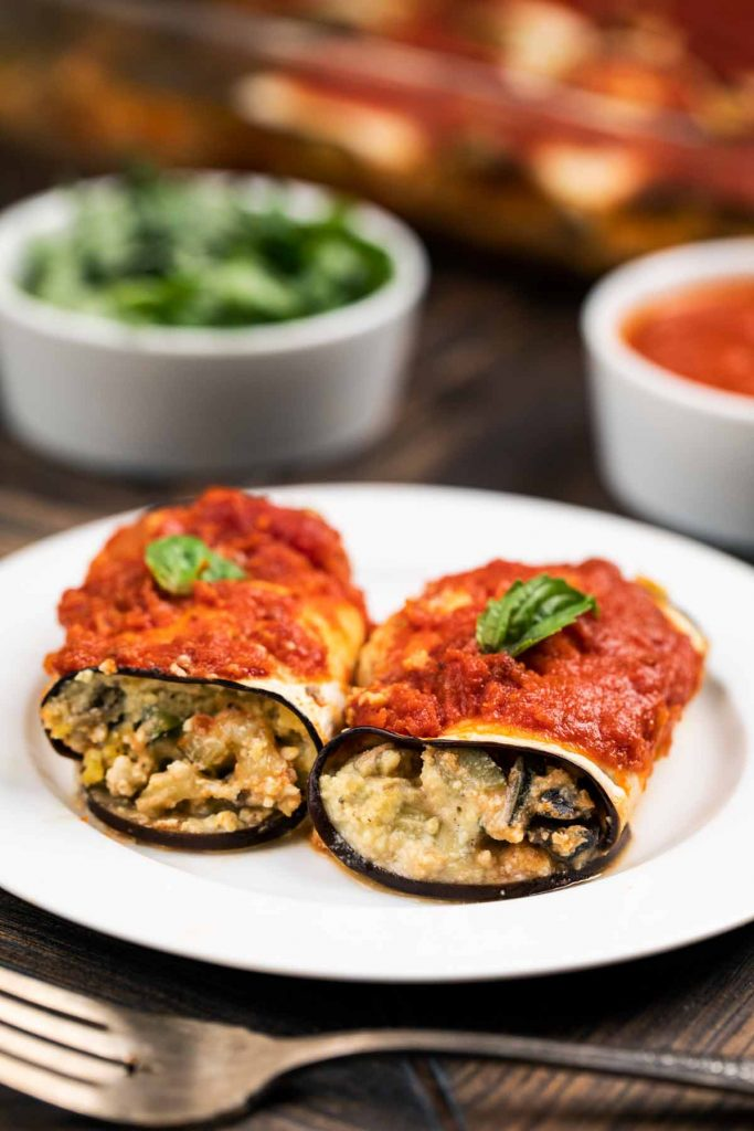 A white plate with 2 eggplant rolls ups with fresh basil on top.