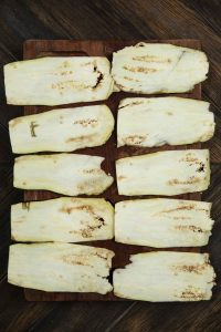 An overhead shot of sliced eggplants placed on a wooden chopping board