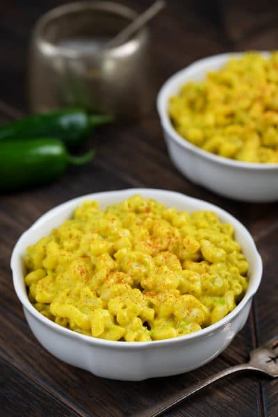 A white bowl filled with macaroni noodles sprinkled with cayenne green peppers and a bowl of mac and cheese in the background