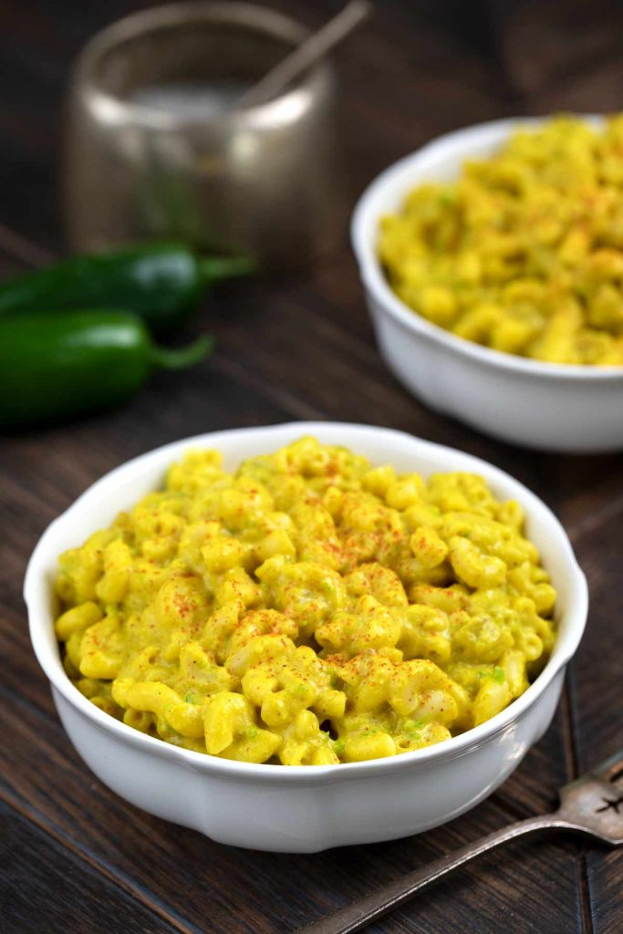 A bowl of Green Chile Mac and Cheese with a sprinkle of cayenne pepper on top and jalapeños in the background.